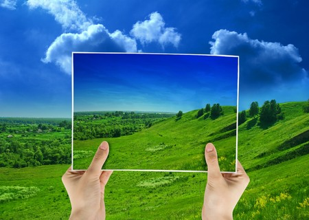 creative pictures: photo of green field in hands on nature background