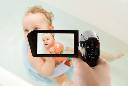 sweet toddler baby boy in bath with ball on camcorder photo