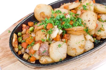 Fried potato with meat and vegetables on a white photo