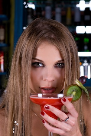 Beauty young woman portrait with a glass drinking a cocktail at a bar Stock Photo - 7607755