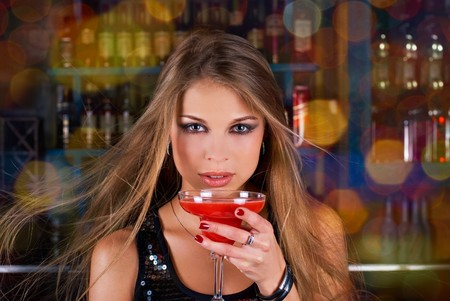 Beauty young woman portrait with a glass drinking a cocktail at a bar