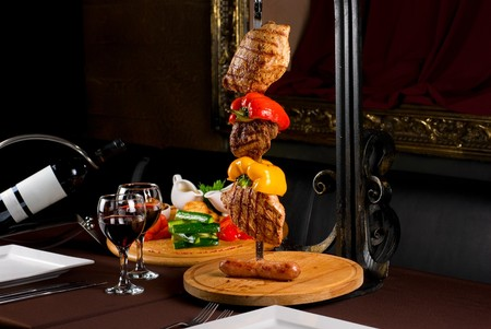 Big tasty roasted meat cuts at skewer on a decorated table Stock Photo - 7608644