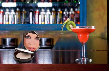 red cocktail with kiwi and cosmetic powder with woman on the wooden bar photo