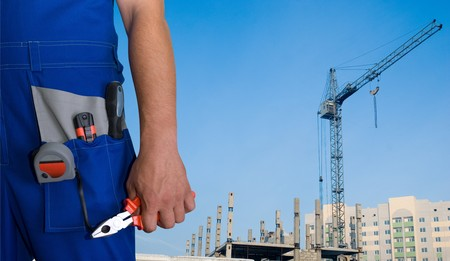 repairman: Closeup of repairman with pliers on building background Stock Photo