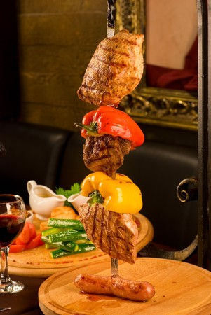 Big tasty roasted meat cuts at skewer on a decorated table