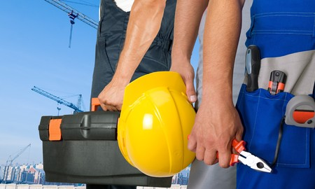 industrial objects equipment: Different workers man closeup on building background Stock Photo