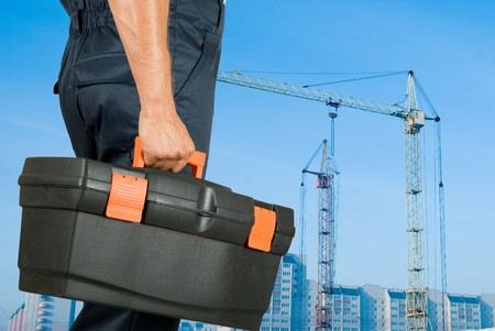 repairman with box of instruments on building background Stock Photo - 7699804