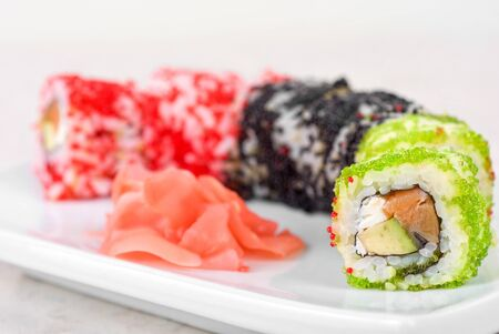 Sushi rolls made of fish avocado and different flying fish roe (tobiko caviar) photo