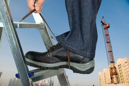 tying: repairman lace his shoes on building background