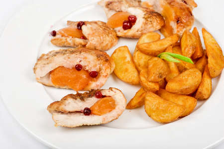 Roast chicken meat with apricot and potato closeup photo