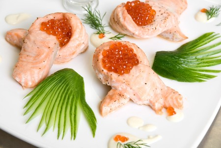 roasted salmon filet with red caviar, cucumbers and sauce photo