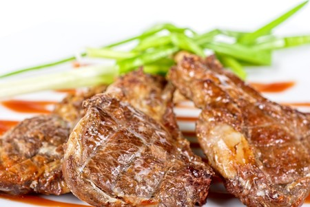 Roasted lamb meat tied with scallion closeup photo