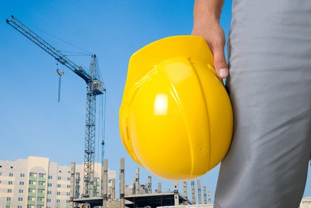 work safe: Closeup of builder with yellow helmet on building panorama background