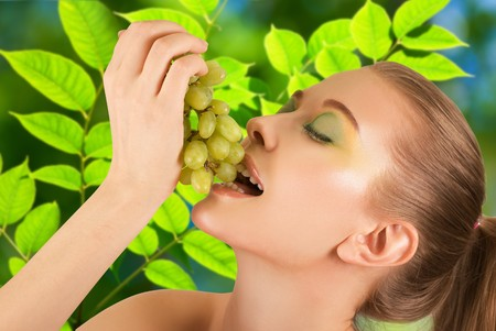 Pretty young woman closeup with grape on the green leaves background photo