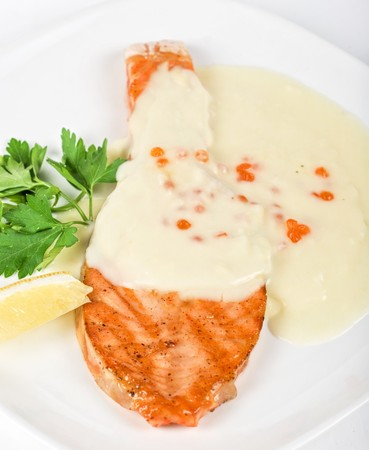 Grilled salmon steak with cheese sauce, greens, lemon and red caviar photo