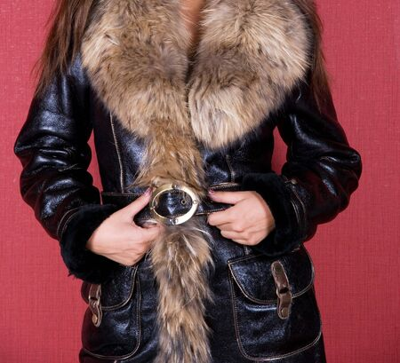fur hood: woman closeup portrait in fur on red background Stock Photo