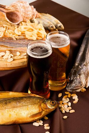 Beer and snacks set: chips, pistachio, shrimp and fish photo