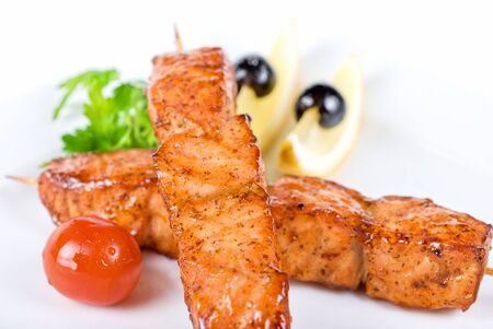 salmon kebab at plate with green lettuce and lemon on a white photo