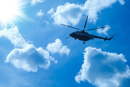 helicopter is flying in blue sunny sky photo