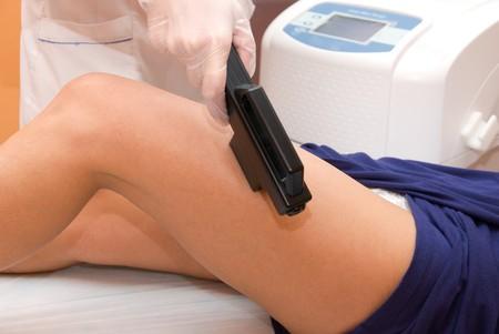 Laser epilation of leg in a modern beauty shop photo
