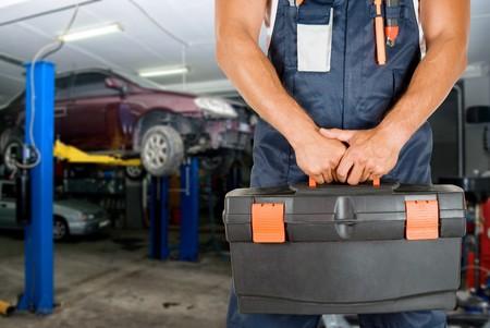 auto hoist: Auto mechanics closeup standing in his workshop