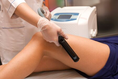 Laser epilation of leg in a modern beauty shop Stock Photo