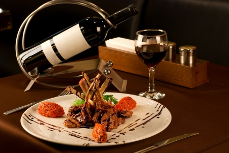 french cuisine: Roasted lamb chops with vegetables on decorated table