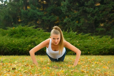 Beauty female doing push ups in the park Stock Photo - 8006870