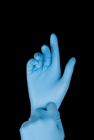gloving up: Blue gloves on a hand on a black background Stock Photo