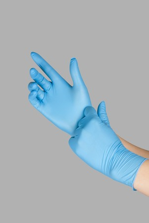 Blue gloves on a hand on a grey background