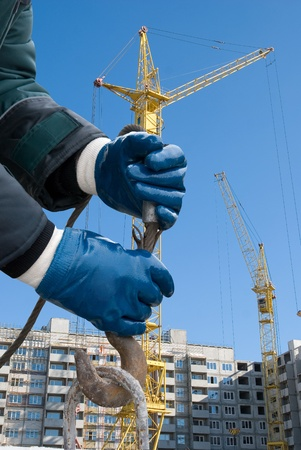 man hands closeup with crane hook at building background photo