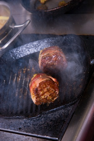 Tasty beef steak grilling in a cast-iron ribbed fry pan photo
