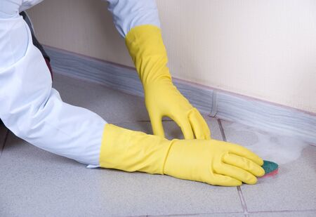 Hands in yellow gloves with sponge, washing floor and plinth photo