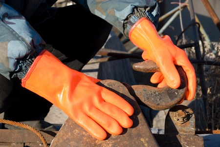 Closeup of worker man at orange gloves