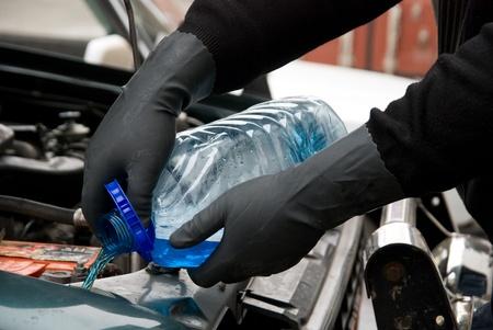 fills: The mechanic fills washing liquid to the car