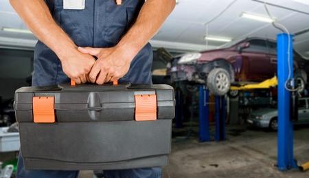 Auto meccanica alzato in piedi nel suo laboratorio