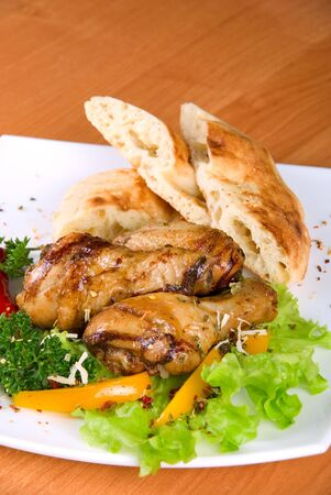 roasted chicken drumstick garnished with fresh green salad, pepper and greens photo