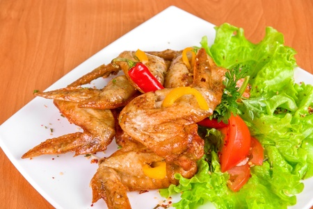 roasted chicken wings garnished with fresh green salad, pepper and greens photo
