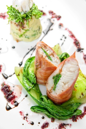 Tasty dish of pike perch at bacon with basilica, lettuce, dill, parsley, pepper and quail egg photo