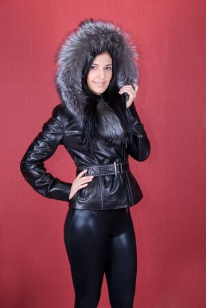 beautiful woman in a fur coat on a red background photo