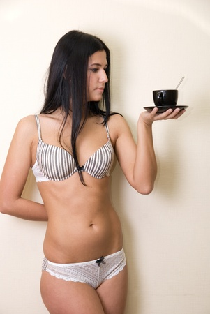 Sexy girl in lingerie at wall background with coffee cup Stock Photo - 8693134