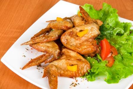 Ali di pollo arrosto, guarniti con verdi, pepe e insalata verde