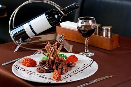 comida gourment: Chuletas de cordero asado con verduras en mesa decorada