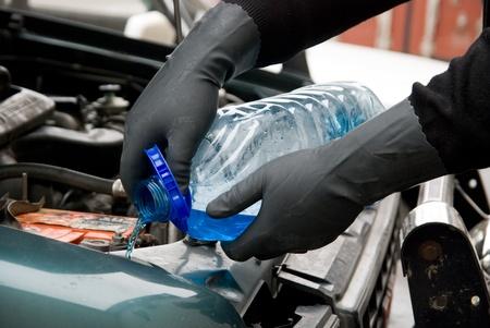 The mechanic fills washing liquid to the car