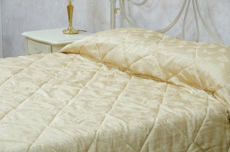 Close up view of a yellow quilt in a bedroom photo