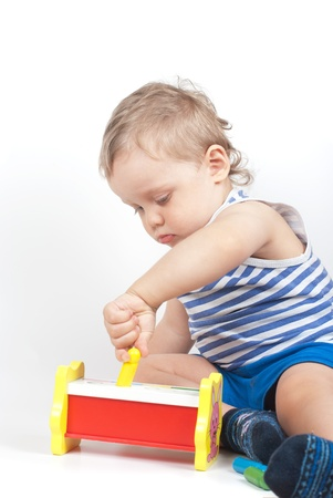 Small baby boy with a toy on white Stock Photo - 8920115