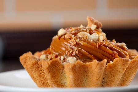 fresh baked cupcake with nuts on a wooden table photo