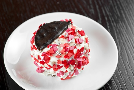 fresh baked cupcake with hearts on a wooden table photo