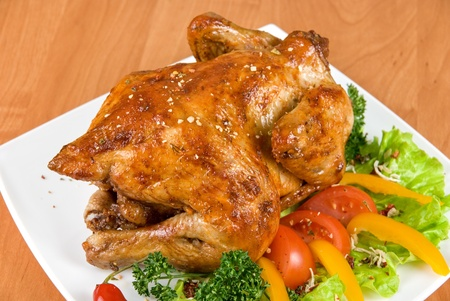 crispy: roasted chicken garnished with fresh tomatoes, green salad, pepper and greens Stock Photo