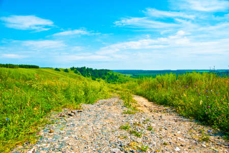 Rural road,blue sky and green grass Stock Photo - 9160347